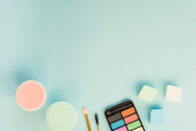 Top view of cosmetics products over turquoise background