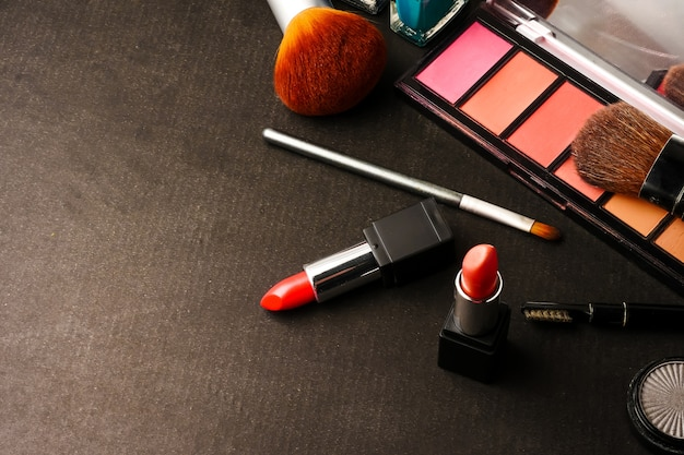 Top view of cosmetics set for makeup on a black background. free space for text.