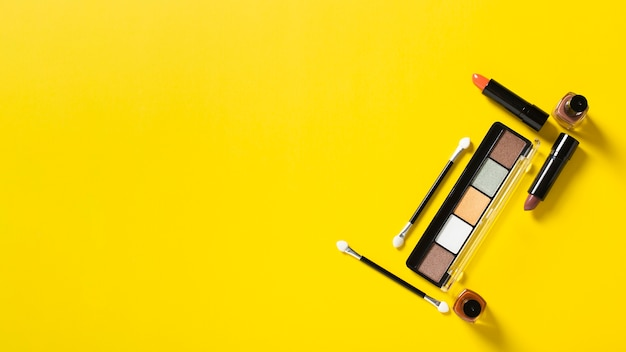 Top view of cosmetics on yellow background with copy space