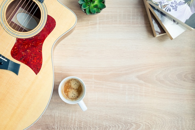 Top view of cosy home scene. guitar, books, cup of coffee, phone and succulent plants over wood. copy space, mock-up.
