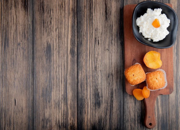 Top view of cottage cheese in a black bowl with muffins and dried apricots on wood cutting board on rustic with copy space