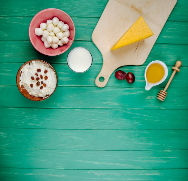 Top view of cottage cheese in a bowl topped with raisins  mozzarella and a piece of dutch cheese on wood cutting board with honey on green wood with copy space