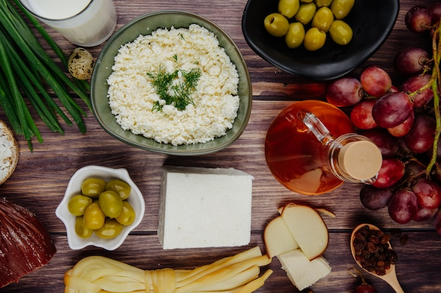 Vista dall'alto di ricotta con erbe in una ciotola e vari tipi di formaggio con miele in una bottiglia di vetro uva fresca e olive in salamoia su legno rustico