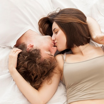 トップビューカップルがベッドでキス