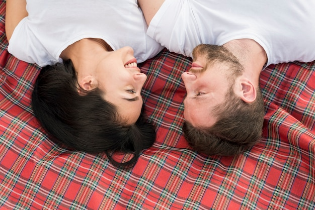 Top view couple laying on picnic blanket