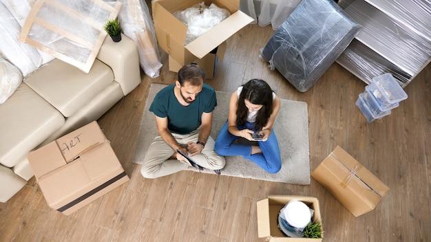Vista dall'alto della coppia che si trasferisce utilizzando il tablet. coppia allegra