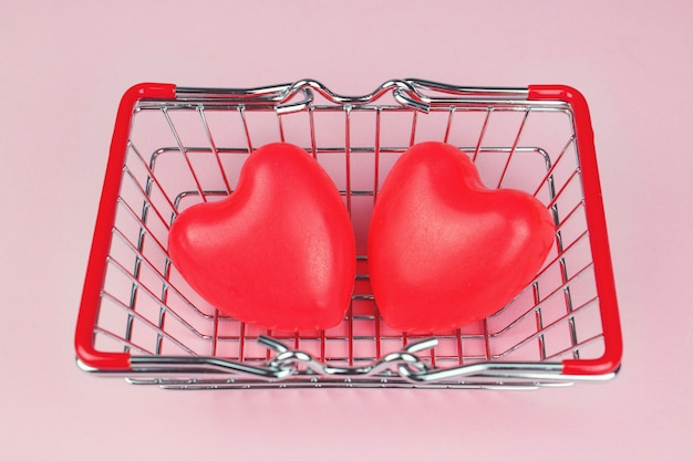 Top view couple red heart shape with mini shopping cart on pink pastel background. love