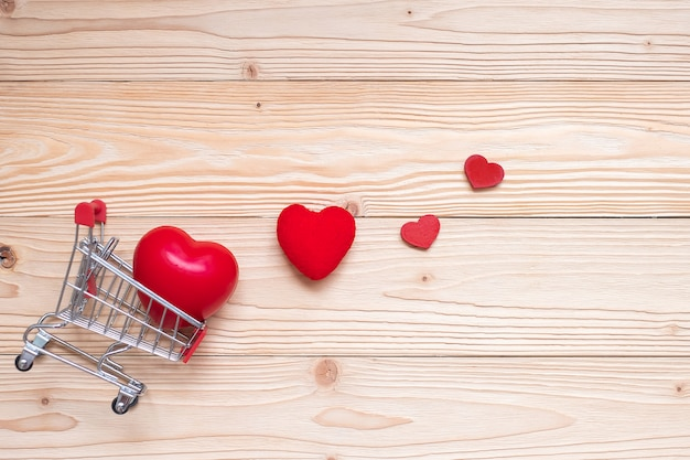 Top view couple red heart shape with mini shopping cart on  wooden table