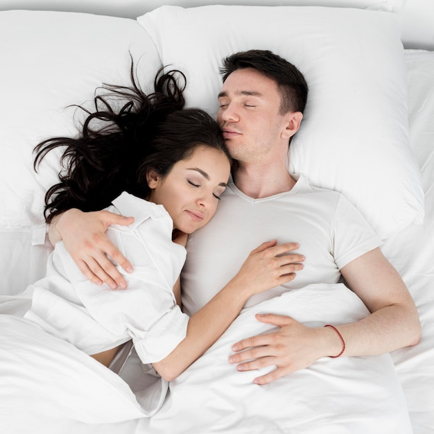 Top view of couple sleeping together in bed