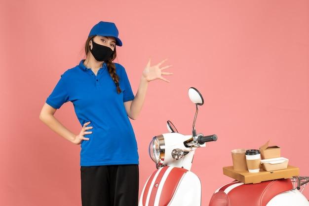Vista dall'alto della ragazza del corriere in maschera medica in piedi accanto alla motocicletta con sopra una torta di caffè su sfondo color pesca pastello