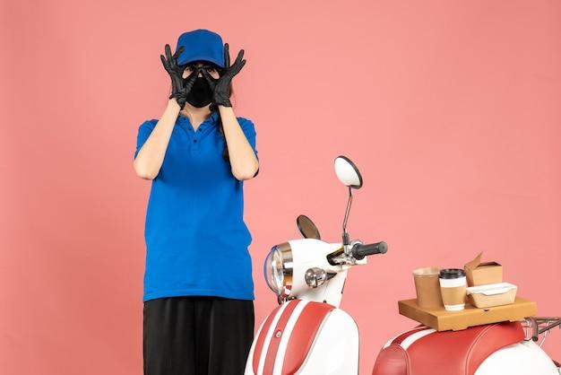 Vista dall'alto della ragazza del corriere in maschera medica in piedi accanto alla moto con una torta di caffè su di essa che fa il gesto degli occhiali su sfondo color pesca pastello