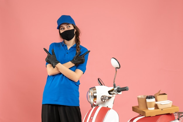 Vista dall'alto della ragazza del corriere in maschera medica in piedi accanto alla moto con una torta di caffè su di essa che punta entrambi i lati su uno sfondo color pesca pastello