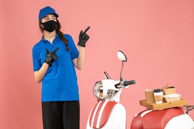 Vista dall'alto della ragazza del corriere in maschera medica in piedi accanto alla moto con una torta di caffè su di essa rivolta verso l'alto su sfondo color pesca pastello