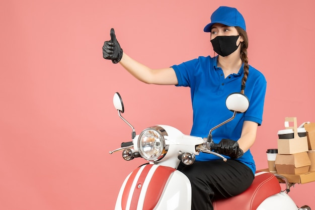 Top view of courier girl wearing medical mask and gloves sitting on scooter delivering orders making ok gesture on pastel peach background