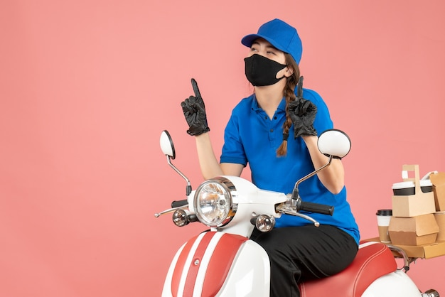 Vista dall'alto della ragazza del corriere che indossa maschera medica e guanti seduti su uno scooter che consegna gli ordini rivolti verso l'alto su sfondo color pesca pastello