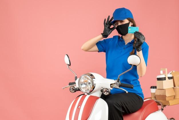 Vista dall'alto della ragazza del corriere che indossa maschera medica e guanti seduti su uno scooter con in mano una carta di credito che consegna ordini su sfondo color pesca pastello