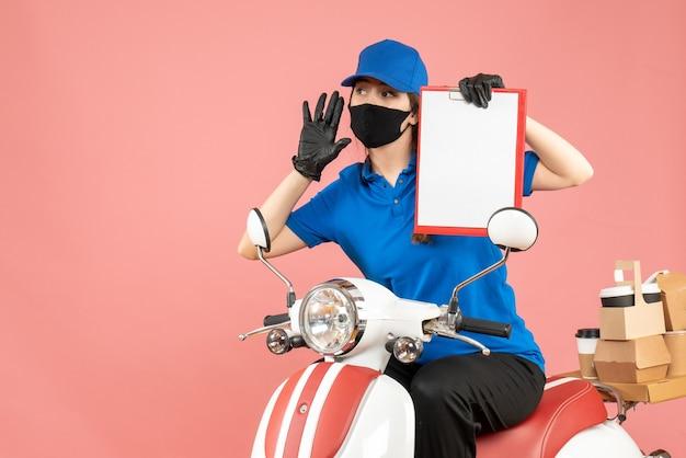 Vista dall'alto della ragazza del corriere che indossa maschera medica e guanti seduti su uno scooter con in mano un foglio di carta vuoto che consegna ordini su sfondo color pesca pastello
