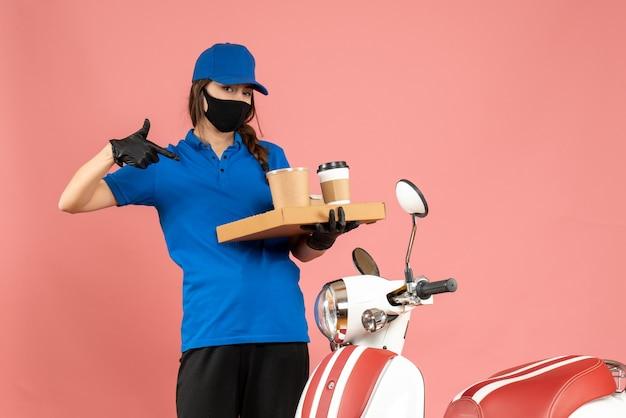 Vista dall'alto della ragazza del corriere che indossa guanti con maschera medica in piedi accanto alla motocicletta che indica piccole torte di caffè su sfondo color pesca pastello