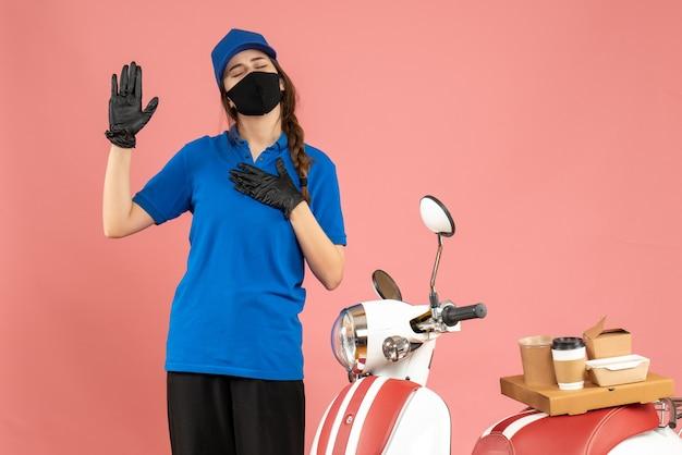 Vista dall'alto della ragazza del corriere che indossa guanti con maschera medica in piedi accanto alla moto con una torta di caffè su di essa che sogna su uno sfondo color pesca pastello Foto Gratuite