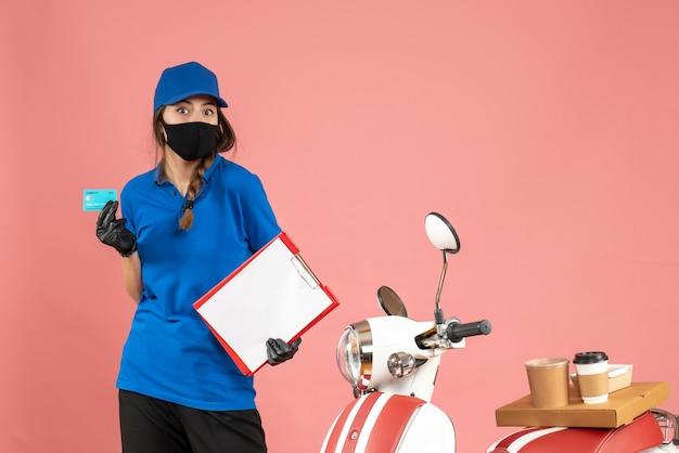 Vista dall'alto della ragazza del corriere che indossa guanti con maschera medica in piedi accanto alla motocicletta con una torta di caffè su di essa che tiene documenti carta di credito su sfondo color pesca pastello