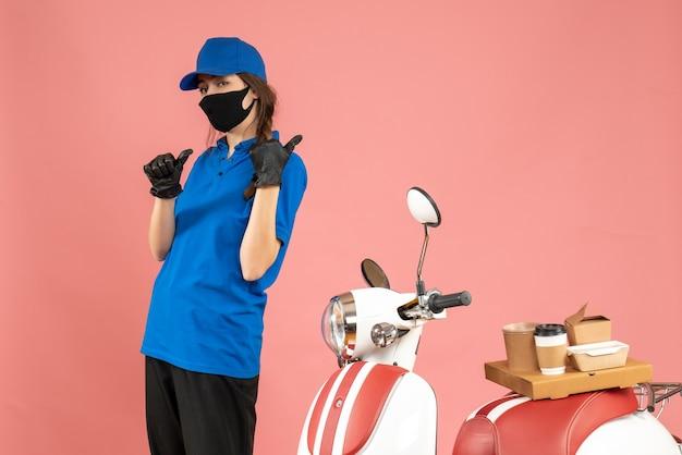 Vista dall'alto della ragazza del corriere che indossa guanti con maschera medica in piedi accanto alla moto con una torta di caffè su di essa che punta indietro su uno sfondo color pesca pastello