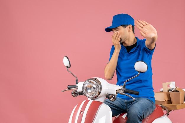 Vista dall'alto del corriere che indossa un cappello seduto su uno scooter che consegna gli ordini facendo un gesto di arresto su sfondo color pesca pastello