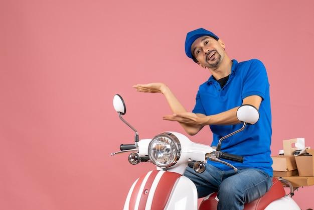 Vista dall'alto del corriere che indossa un cappello seduto su uno scooter che consegna ordini indicando qualcosa su sfondo color pesca pastello