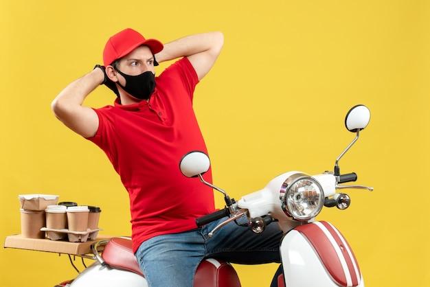 Vista dall'alto del ragazzo del corriere che indossa guanti di camicetta e cappello rossi nella mascherina medica che consegna l'ordine che si siede sullo scooter che si sente confuso