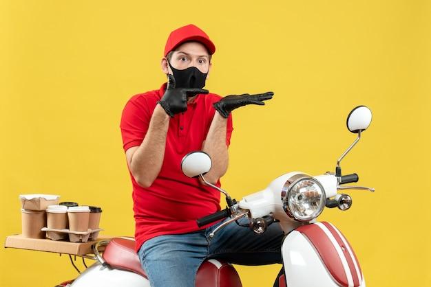 Vista superiore del ragazzo del corriere che indossa guanti di camicetta e cappello rossi nella mascherina medica che consegna l'ordine che si siede sullo scooter che si sente curioso
