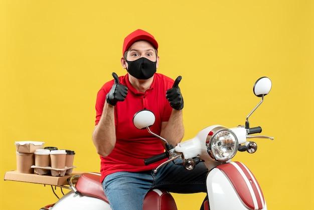 Vista superiore del ragazzo del corriere che indossa la camicetta rossa e guanti del cappello nella mascherina medica che trasporta l'ordine che si siede sullo scooter che si sente sorpreso facendo il gesto giusto