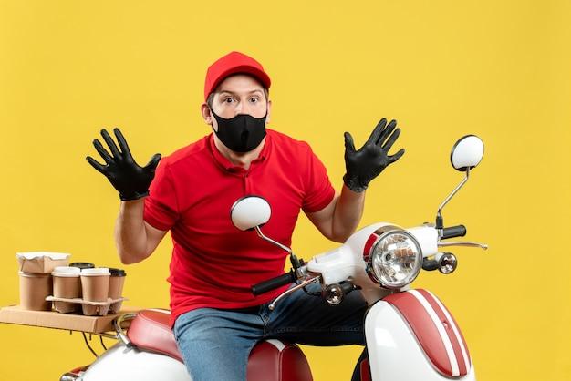 Vista superiore del ragazzo del corriere che indossa guanti di camicetta e cappello rossi in maschera medica che consegna l'ordine seduto sullo scooter focalizzato su qualcosa con un'espressione facciale confusa