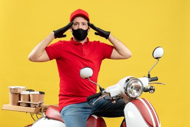 Vista superiore del ragazzo del corriere che indossa guanti di camicetta e cappello rossi nella mascherina medica che consegna l'ordine che si siede sullo scooter si è concentrato su qualcosa