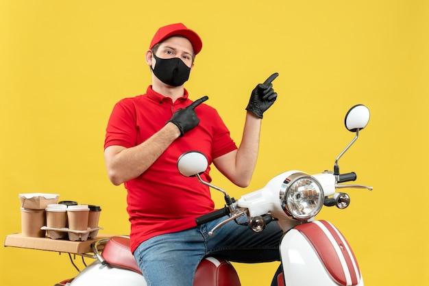 Vista superiore del ragazzo del corriere che indossa guanti di camicetta e cappello rossi nella mascherina medica che consegna l'ordine che si siede sullo scooter che indica verso l'alto