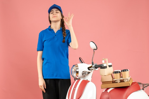 Top view of courier lady standing next to motocycle with coffee and small cakes on it making eyeglasses gesture on pastel peach color background