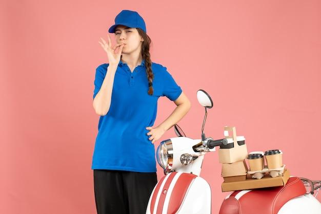 Vista dall'alto della signora del corriere in piedi accanto alla motocicletta con caffè e piccole torte su di essa facendo un gesto perfetto su uno sfondo color pesca pastello