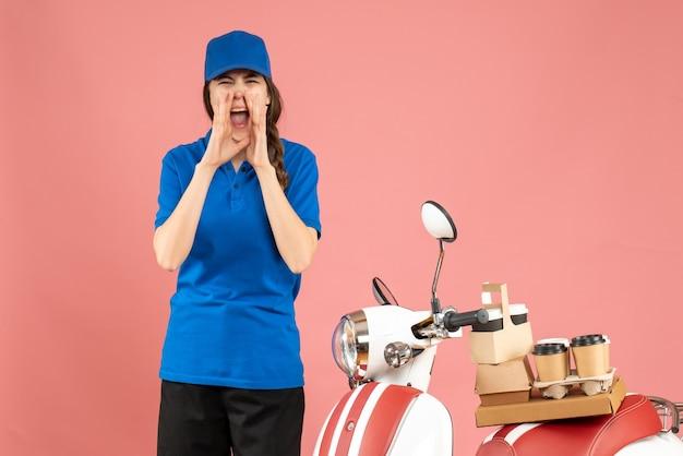 Vista dall'alto della signora del corriere in piedi accanto alla moto con caffè e piccole torte che chiama qualcuno su uno sfondo color pesca pastello