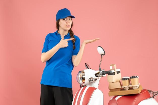 Vista dall'alto della signora del corriere in piedi accanto alla moto con caffè e piccole torte su di essa che punta qualcosa sul lato sinistro su sfondo color pesca pastello