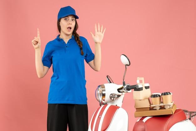 Vista dall'alto della signora del corriere in piedi accanto alla motocicletta con caffè e piccole torte su di essa che mostrano cinque puntate verso l'alto su uno sfondo color pesca pastello