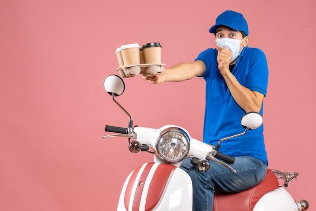 Vista dall'alto dell'uomo del corriere in maschera che indossa un cappello seduto su uno scooter che mostra gli ordini che si sentono confusi su uno sfondo di pesca pastello