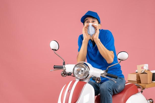 Vista dall'alto del corriere in maschera medica che indossa un cappello seduto su uno scooter che chiama qualcuno su sfondo color pesca pastello peach