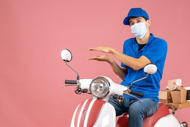 Vista dall'alto del corriere in maschera medica che indossa un cappello seduto su uno scooter che spiega qualcosa su sfondo color pesca pastello