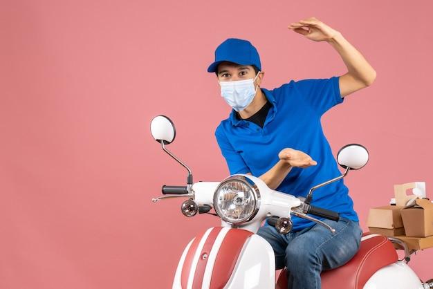 Vista dall'alto dell'uomo corriere in maschera medica che indossa un cappello seduto su uno scooter e che fa qualcosa di esatto su sfondo color pesca pastello