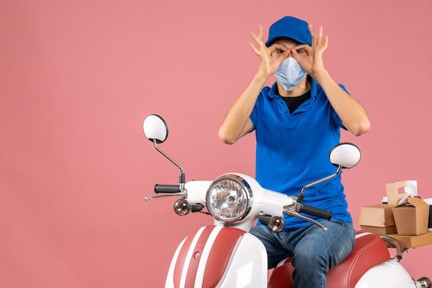 Vista dall'alto del corriere in maschera medica che indossa un cappello seduto su uno scooter e fa il gesto degli occhiali su sfondo color pesca pastello