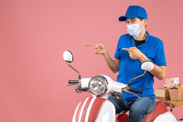 Vista dall'alto del corriere in maschera medica che indossa un cappello seduto su uno scooter su sfondo color pesca pastello peach