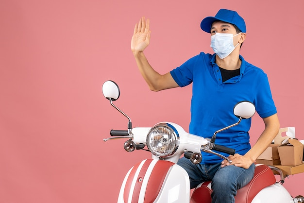 Top view of courier man in medical mask wearing hat sitting on scooter saying hello to someone on pastel peach background