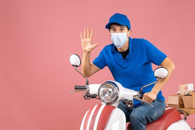 Vista dall'alto del corriere in maschera medica che indossa un cappello seduto su uno scooter e ne mostra cinque su sfondo color pesca pastello