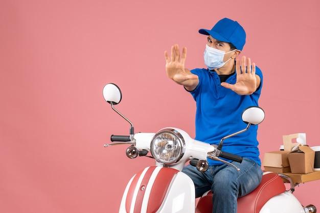 Vista dall'alto dell'uomo corriere in maschera medica che indossa un cappello seduto su uno scooter e mostra dieci su sfondo color pesca pastello