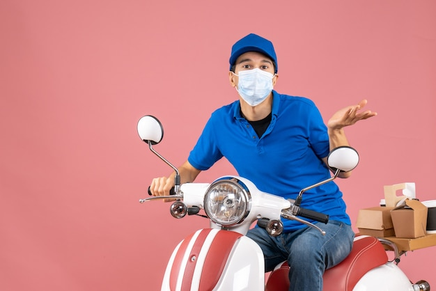 Top view of courier man in medical mask wearing hat sitting on scooter wondering something on pastel peach background