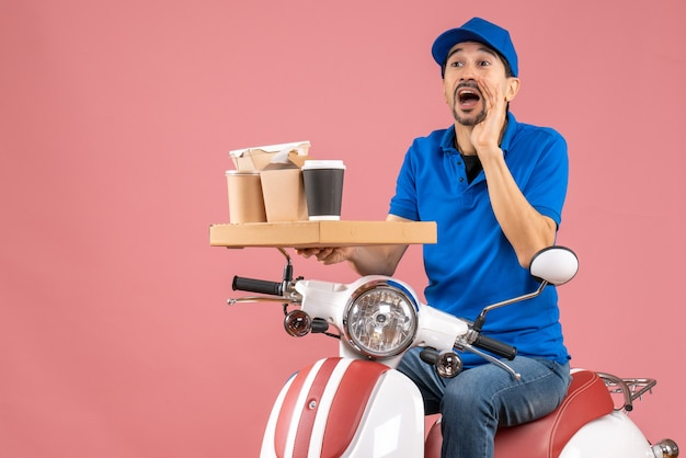 Top view of courier man wearing hat sitting on scooter calling someone on pastel peach background