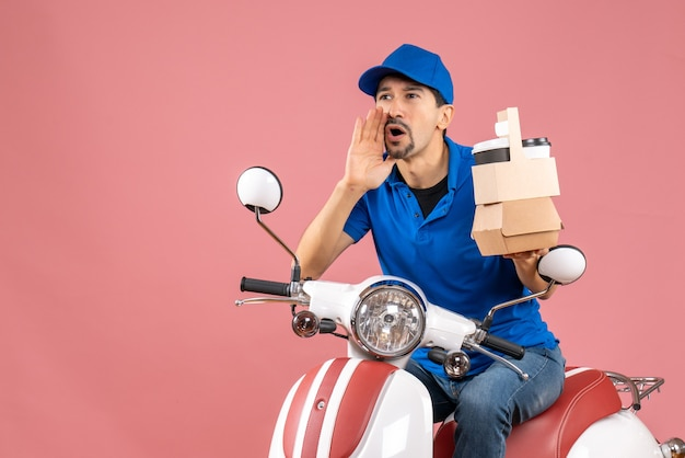 Top view of courier man wearing hat sitting on scooter holding orders calling someone on pastel peach background